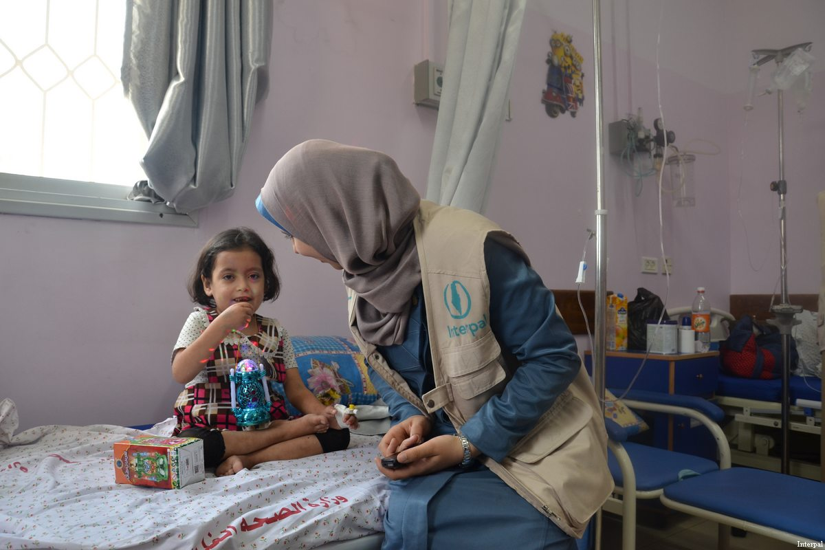An Interpal aid worker seen with a Palestinian child in hospital
