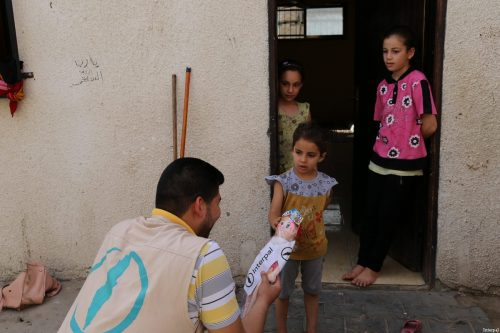 Interpal staff distribute aid to Palestinian refugee child